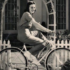 Deanna Durbin rides a bike.