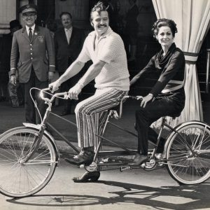 Robert Goulet and Carol Lawrence ride a bike.