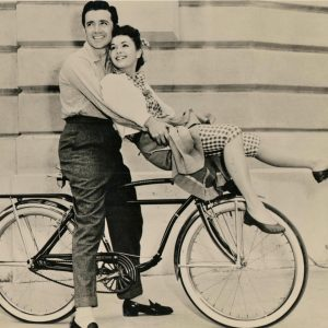 Vic Damone and Debbie Reynolds ride a bike.