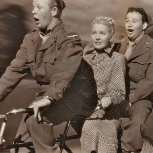 Bill Murphy, Jean Arthur and Stanley Prager ride a bike.