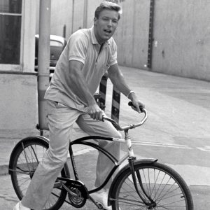 Richard Chamberlain rides a bike.