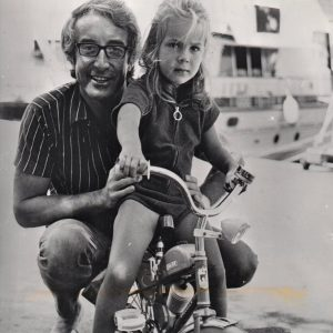 Victoria Sellers rides a bike, Peter Sellers stands by.