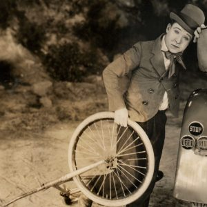 Harry Langdon picks up a bike.