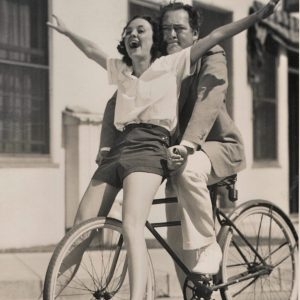 Andrea Leeds and Edward Arnold ride a bike.