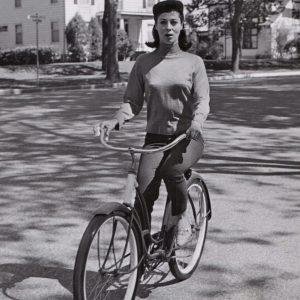 Rita Gam rides a bike.