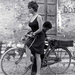 Claudia Cardinale readies to ride a bike, George Chakiris fiddles.