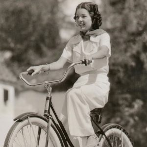 Frances Langford rides a bike.