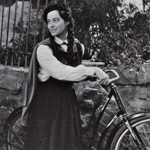 Marisa Pavan walks a bike, goo-goo eyed.