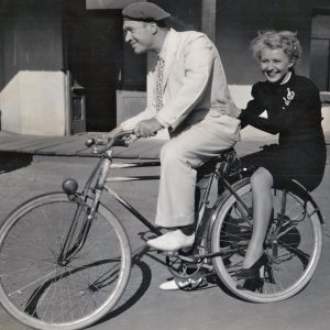 William Newell and Sally Payne ride a bike.