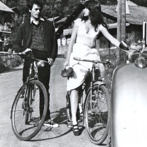 Robert Hossein and Maria Schneider ride bikes.