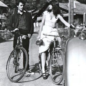 Robert Hossein and Maria Schneider ride bikes.