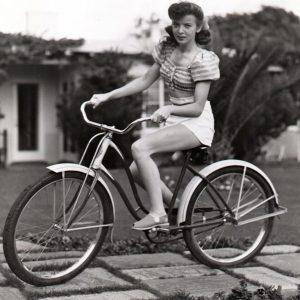Ida Lupino rides a bike.