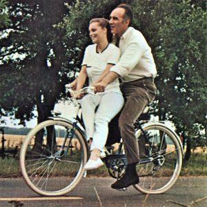 Romy Schneider and Michel Piccoli ride a bike.