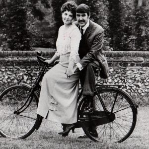Pauline Collins and John Alderton pose on a bike.