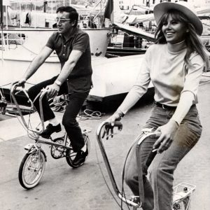 Peter Sellers and Britt Ekland ride bikes.