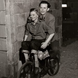 Helen Backlin and David Tomlinson ride a bike.