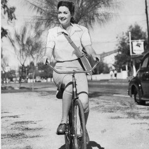 Gail Patrick rides a bike.