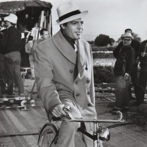Marcello Mastroianni rides a bike.