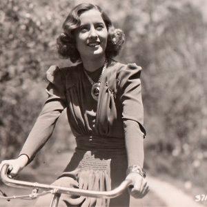 Barbara Stanwyck rides a bike.