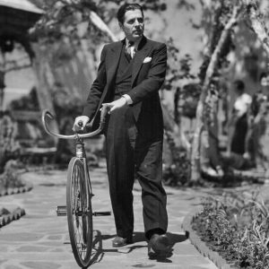 Warner Baxter walks a bike.