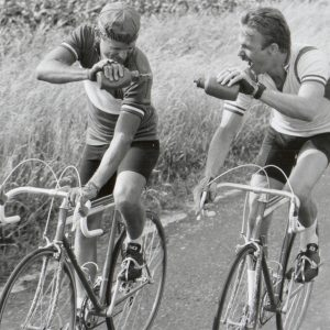David Marshall Grant and Kevin Costner ride bikes, cross-hydrate.