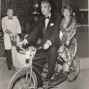 James and Gloria Stewart ride a bike.