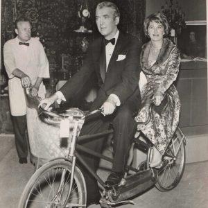 James and Gloria Stewart ride a bike.
