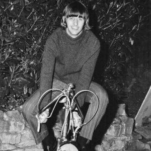 Ringo Starr rides a bike.