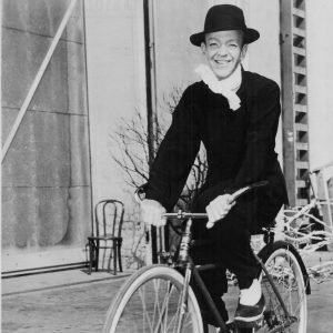 Fred Astaire rides a bike.