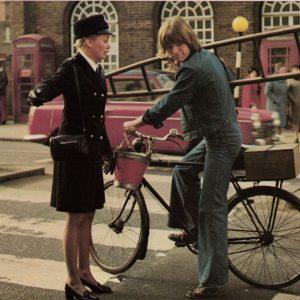 Robin Askwith rides a bike, Linda Hayden stops traffic.