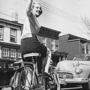 Jan Sterling rides bike, waves goodbye.