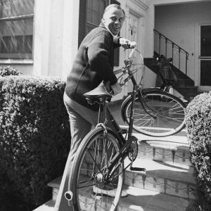 McLean Stevenson carries a bike.