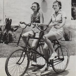 Jean Howard and Irene Hervey ride a buddy bike.