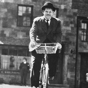 Oliver Hardy rides a bike.