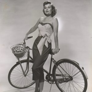 Virginia Mayo poses with bike.