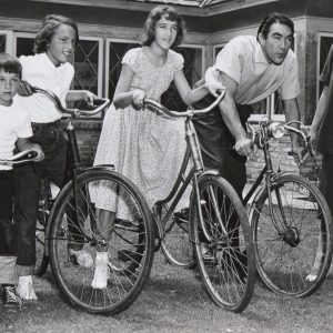 Anthony Quinn and kids ride bikes.