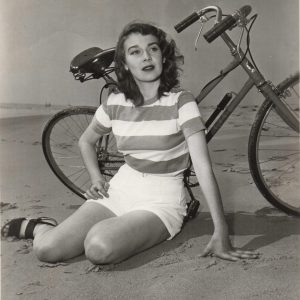 Betsy Drake rests a bike, beach-side.