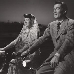Rosalind Russell and Walter Pidgeon ride bikes.