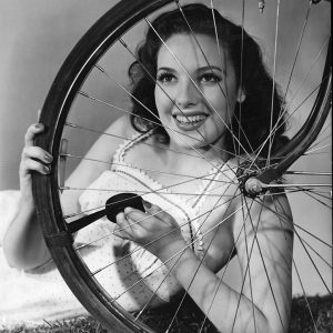 Linda Darnell fixes a bike.