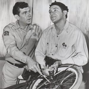 Andy Griffith and George Lindsey fix a bike.
