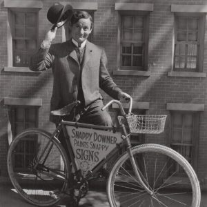 Roscoe Karns rides a bike, tips his hat.