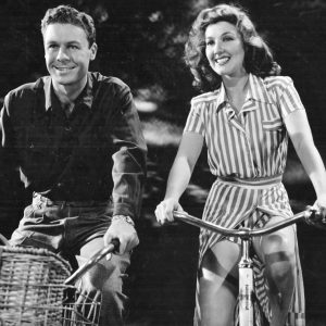 John Archer and Jean Parker ride bikes.