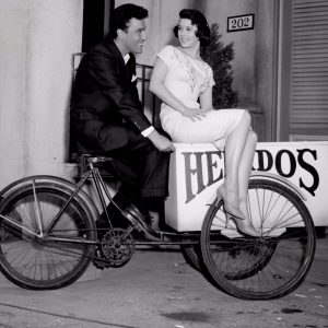 Jill St. John and Nico Minardos ride a delivery bike.