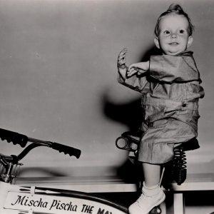 Baby Sandy rides a bike.
