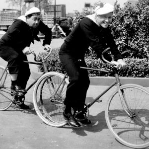 Eugene Pallette and Jack Oakie ride bikes.