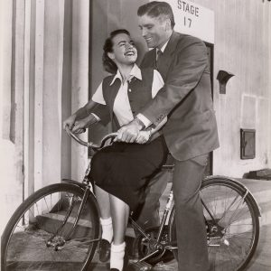 Terry Moore and Burt Lancaster ride a bike.