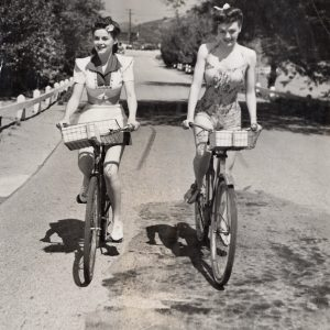 Marguerite Chapman and Leslie Brooks ride bikes.