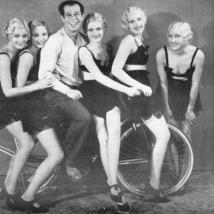 Bert Lahr rides a bike — with chorus girls.