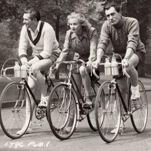 John McCallum, Honor Blackman and Patrick Holt ride bikes.