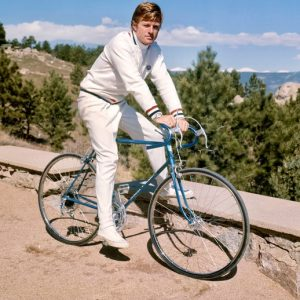 Robert Redford rides a bike.